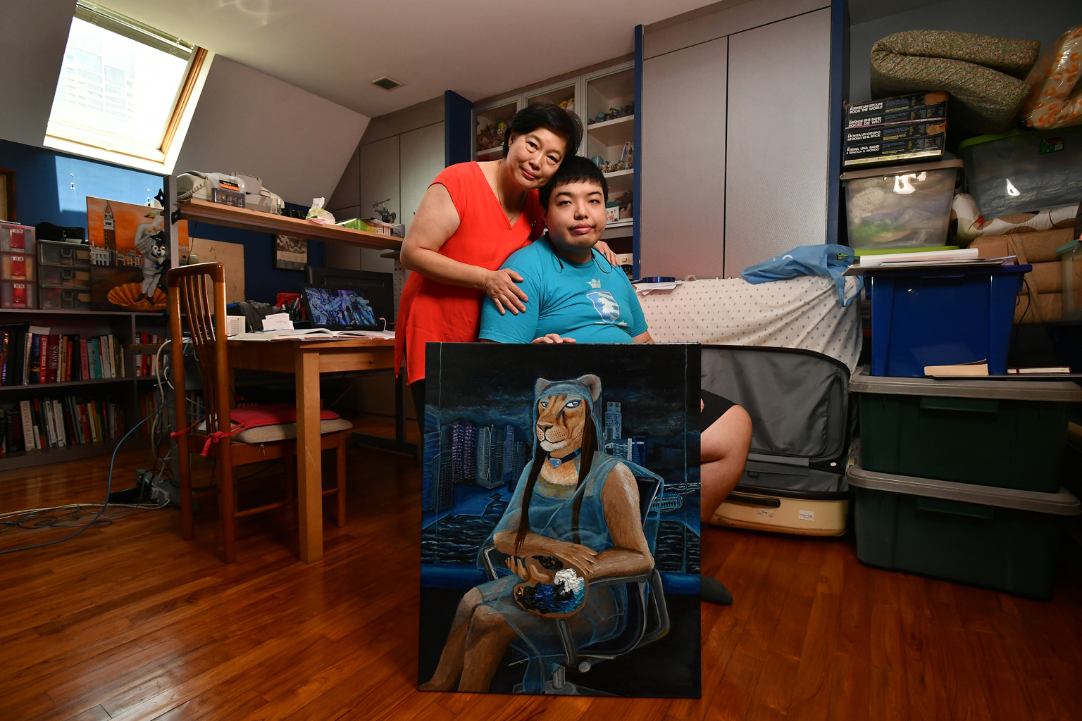 """ST10022017-1704155990-Lim Yaohui/WONG KIM HOH/ //Mrs Leong Geok Hoon, 60, Founder of Adelaide Harvests, with her son, Mr Leong Keat Mun, 24, Undergraduate, at home on Feb 10, 2017. He is holding an acrylic painting, titled """"La Gioconda come una Leonessa - Laboratorio di Fotographia"""" that he painted. //For It Changed My Life series. When her youngest son was diagnosed as autistic, Tan Geok Hoon, a former high flying banker, started raising awareness about the condition including helping to found the Autism Resource Centre. She recently started an online business selling artisanal Aussie products while her autistic son completes his product design degree in Australia. (ST PHOTO: LIM YAOHUI)##########khgeok##########LIM YAOHUI"""